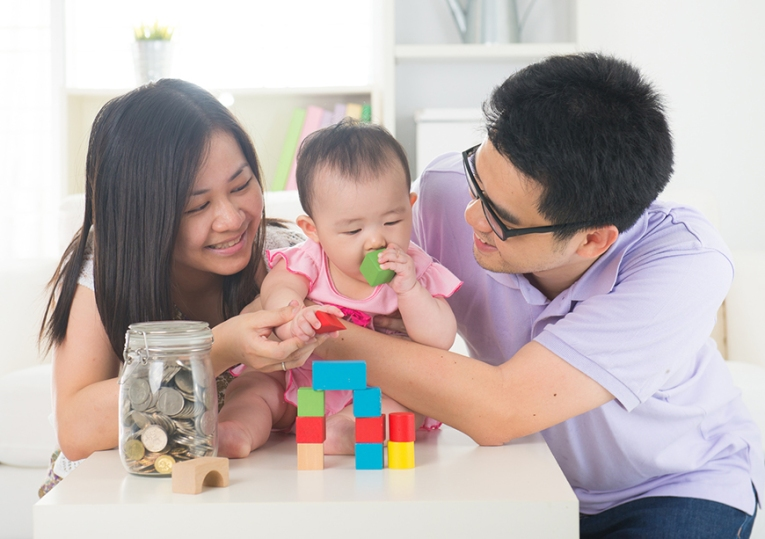 asian parent playing with baby girl in livingroom