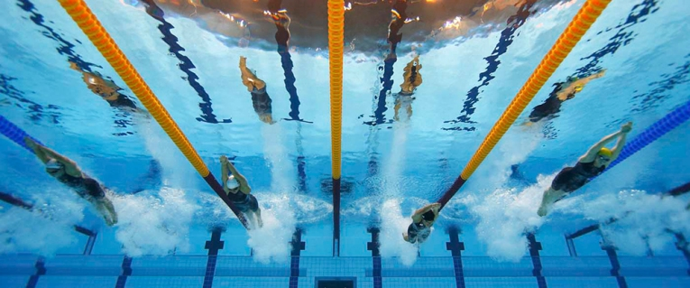 Competitors swim in the women's 200m butterfly heats during the London 2012 Olympic Games